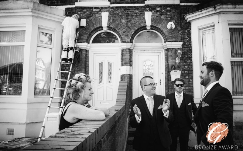The Groom and his friends talk to a neighbour as a decorator paints the front of the house