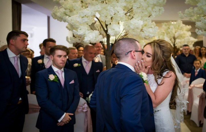 A kiss for the groom as the bride arrives