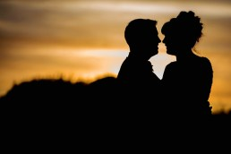 Bride and groom silhouette against sunset sky