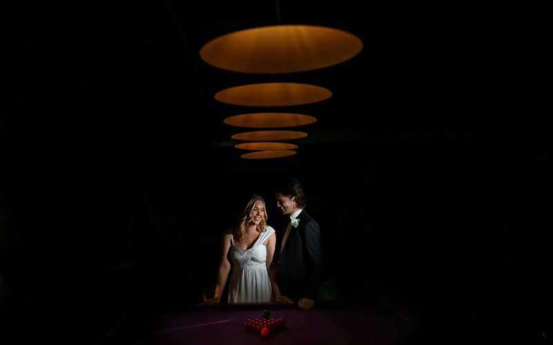 Bride and groom laughing beneath circular light shades