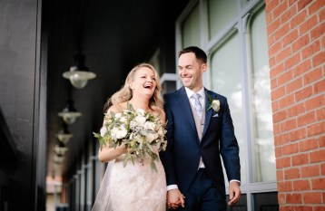 The bride laughs as walks with the groom