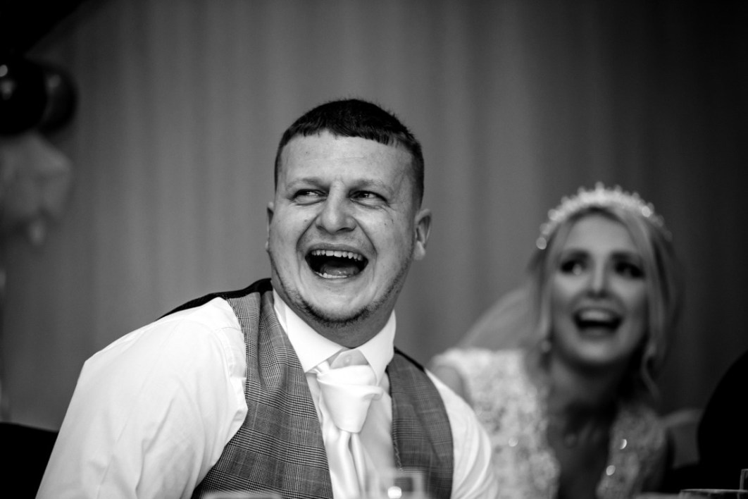 Image of the Groom laughing during speeches  at Wychwood Park