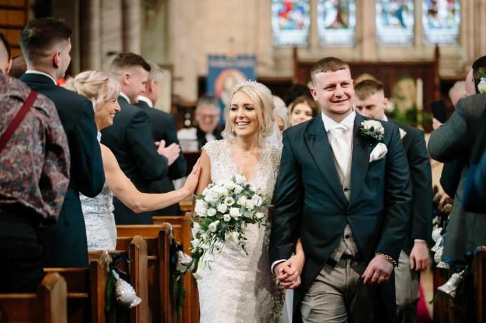 Happy newlyweds leaving church