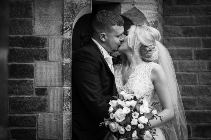 A kiss between the bride and groom as she holds her bouquet