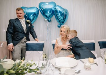 A page boy hugs the bride at the wedding breakfast