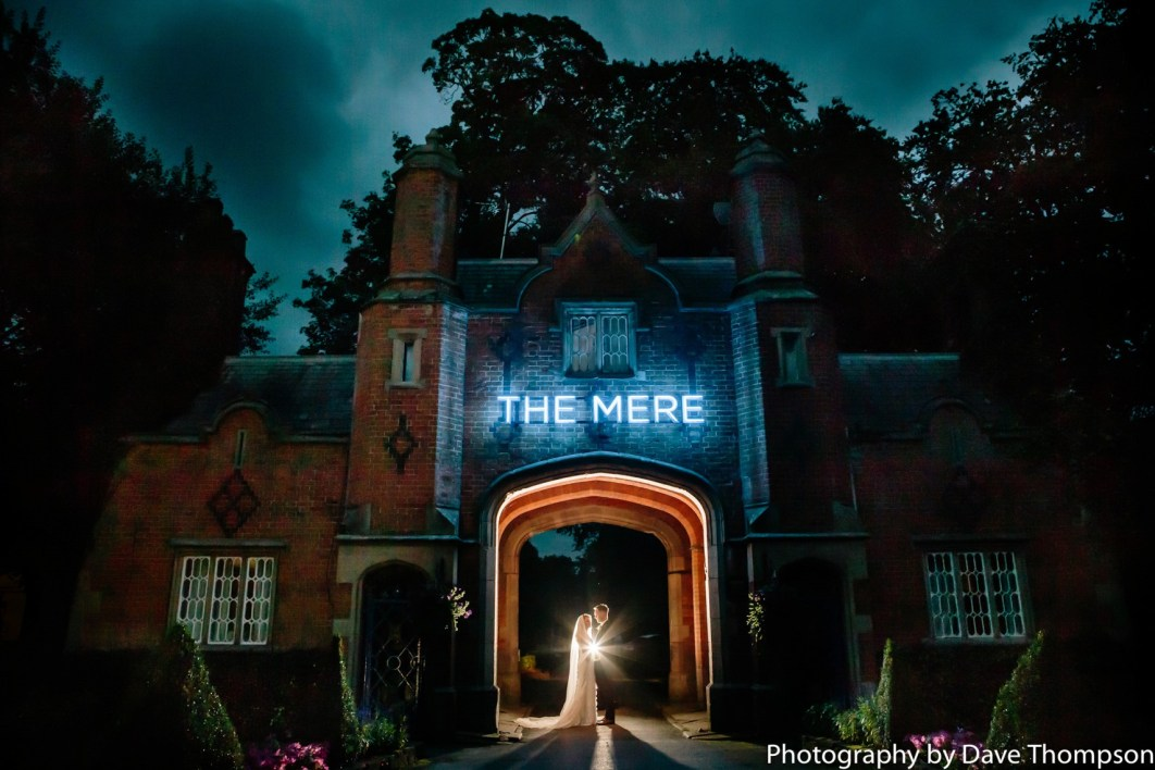 The Bride and Groom beneath the arch at the entrance to The Mere Resort