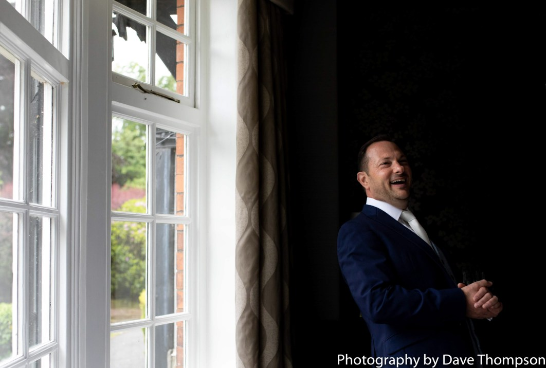 The groom laughs as he talks to guests