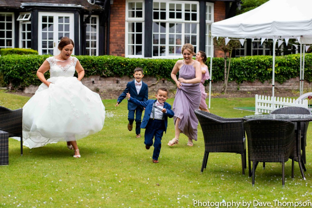 The bride and her bridesmaids chase a page boy.