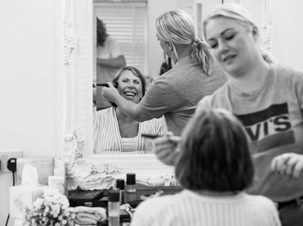 Mother of the bride laughing as she has her make up done
