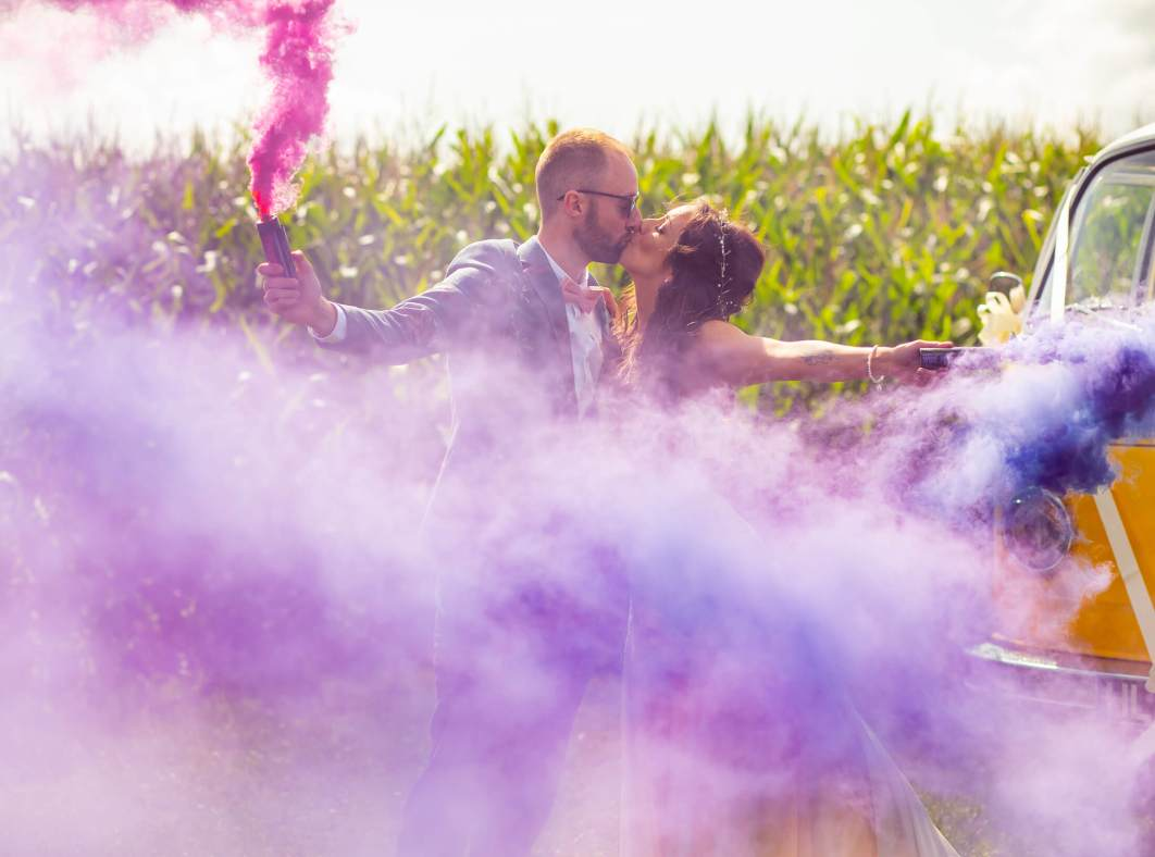 The bride and groom kiss whilst holding smoke grenades