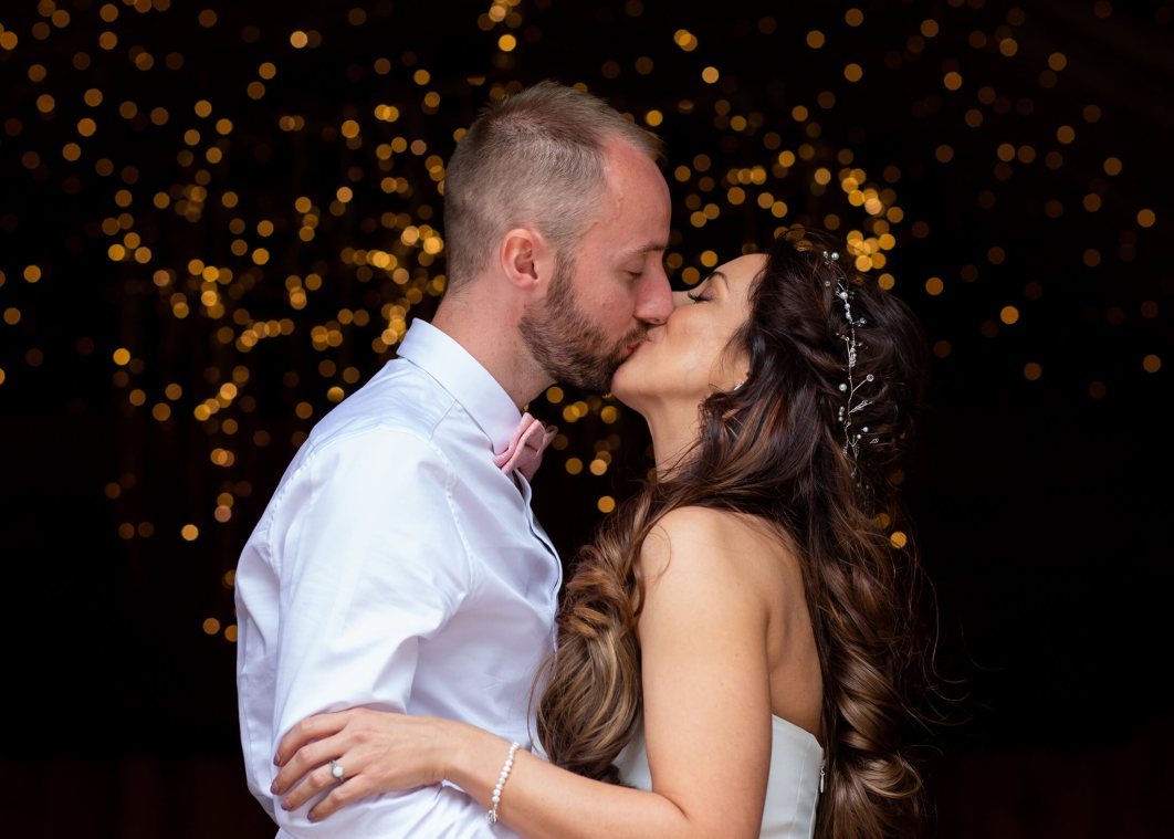 The bride and groom kiss in front of fairy lights.