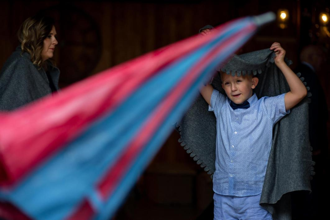 A young boy uses a blanket to keep warm in the rain.