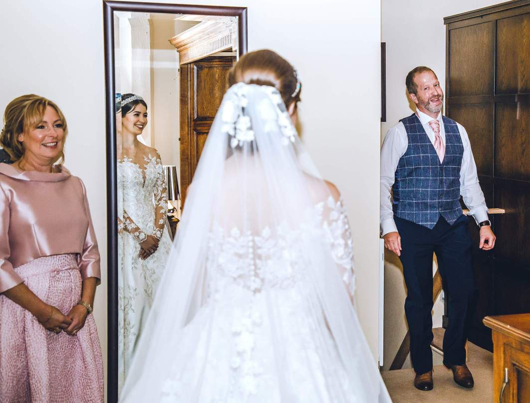 A father sees his daughter in her wedding dress for the first time