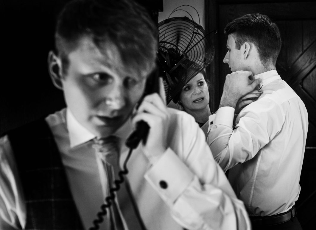 The mother of the groom helps her son with his tie whilst the best man answers a phone call.