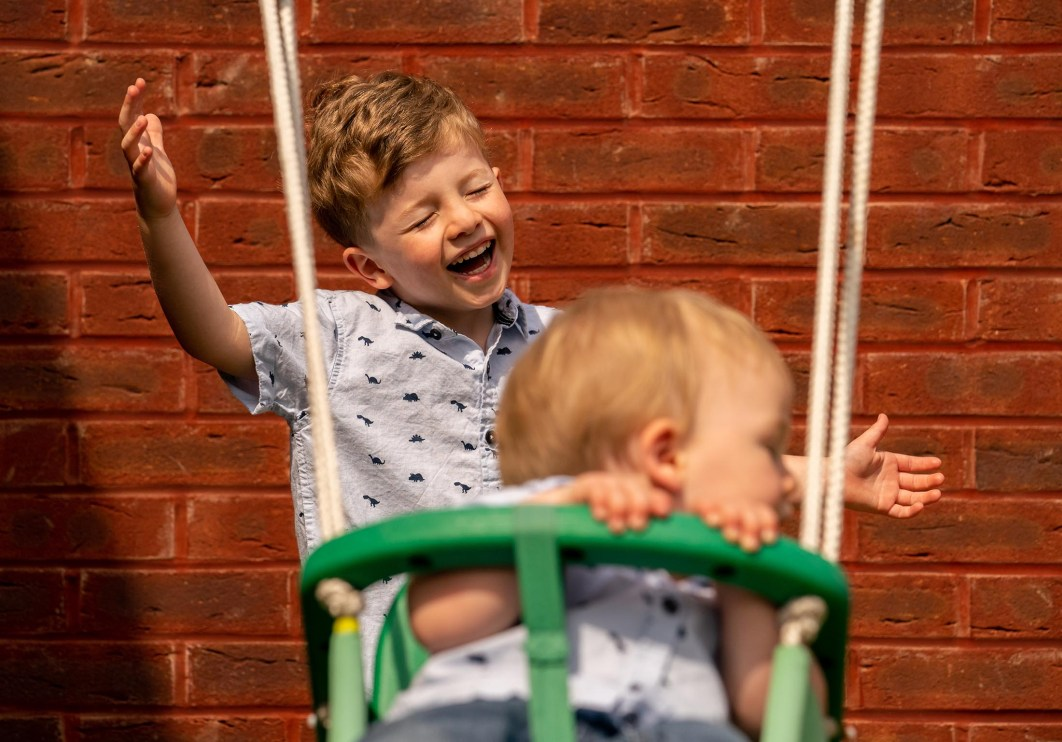 A young boy laughs as he pushes his little brother on the swings.