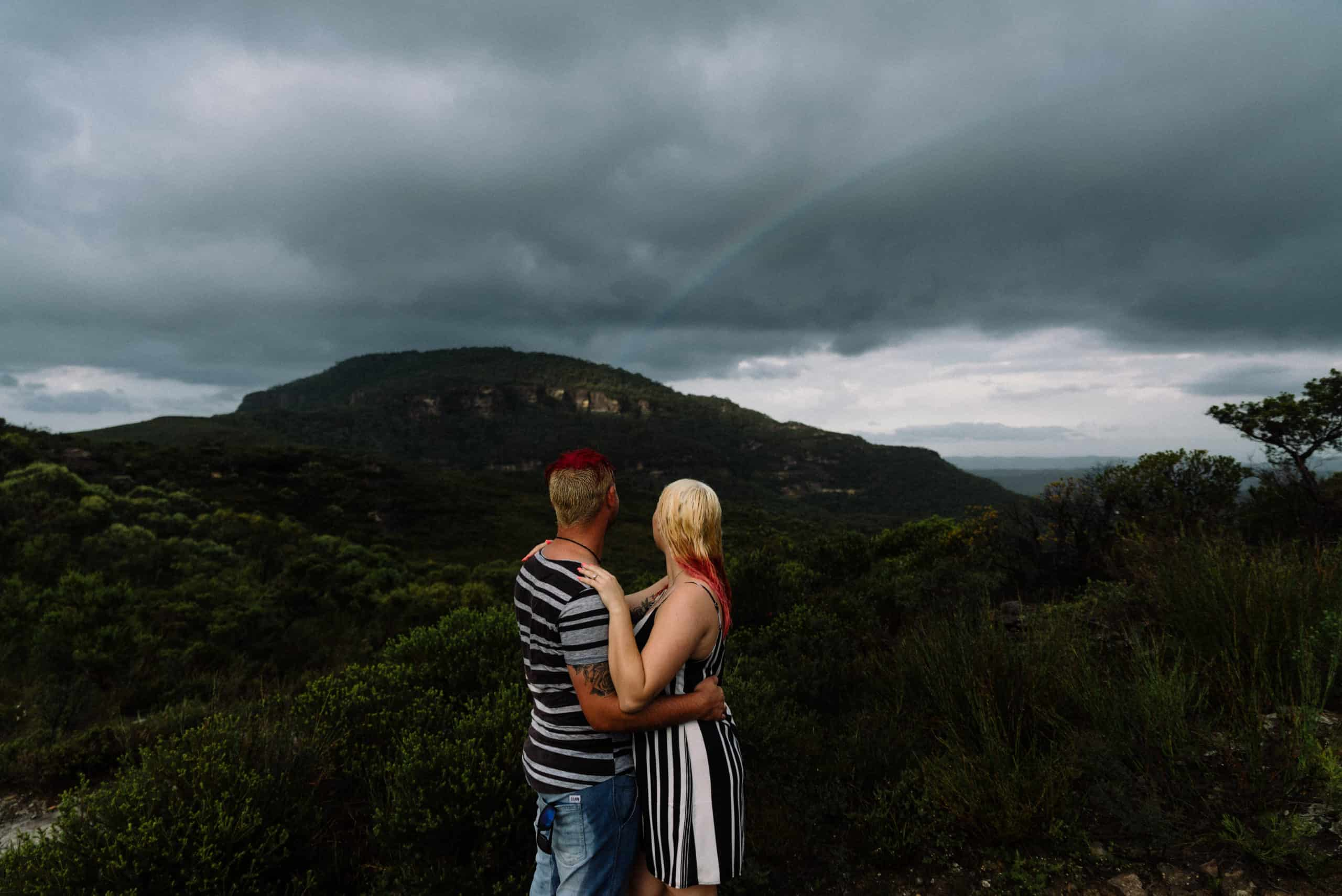 top engagement photoshoot location bride and groom embracing and enjoying rainbow over the mountains