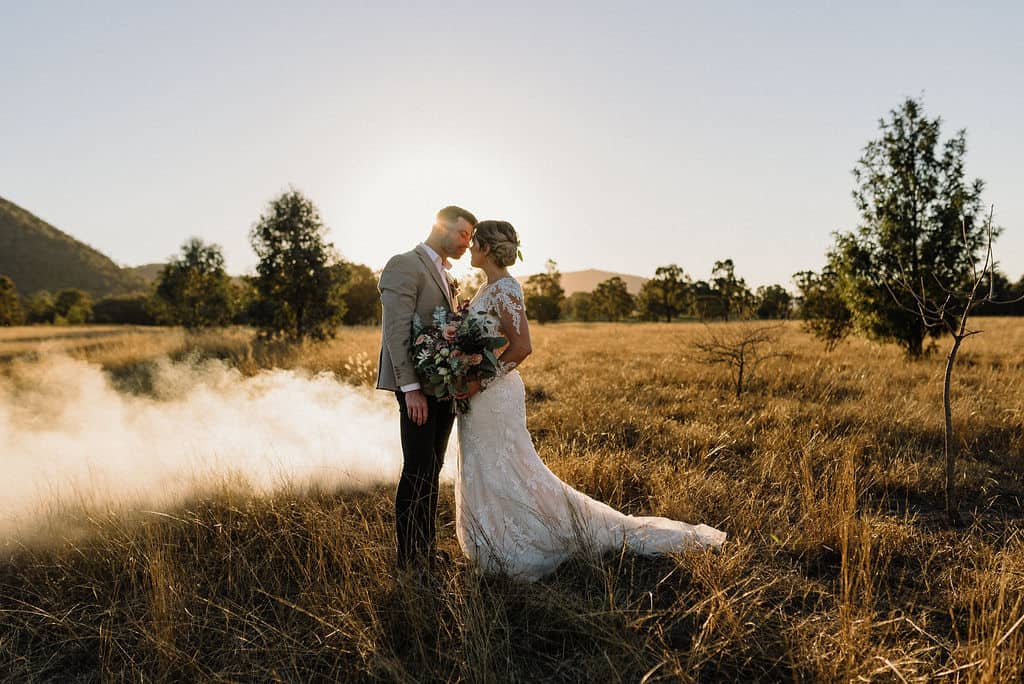 bride and groom enjoying first kiss as the sun sets across a field behind them in the gorgeous hunter valley