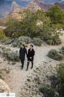 Two newly engaged men walk holding hands at Grand Canyon