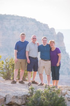 family poses at Grand Canyon for a photo
