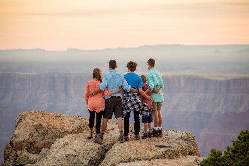 family looks off at a grand canyon viewpoint