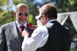The groons dada putting the buttoner on the brides dad