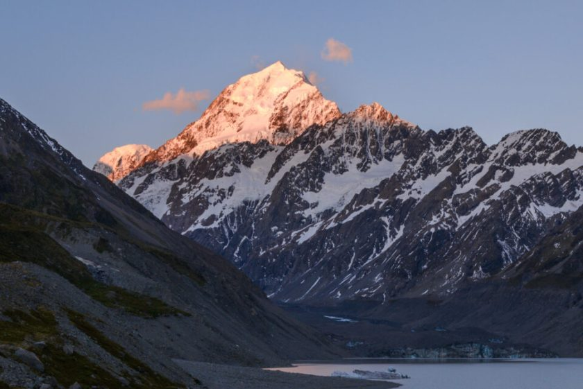 Mountain with bright sunlit peak at sunset