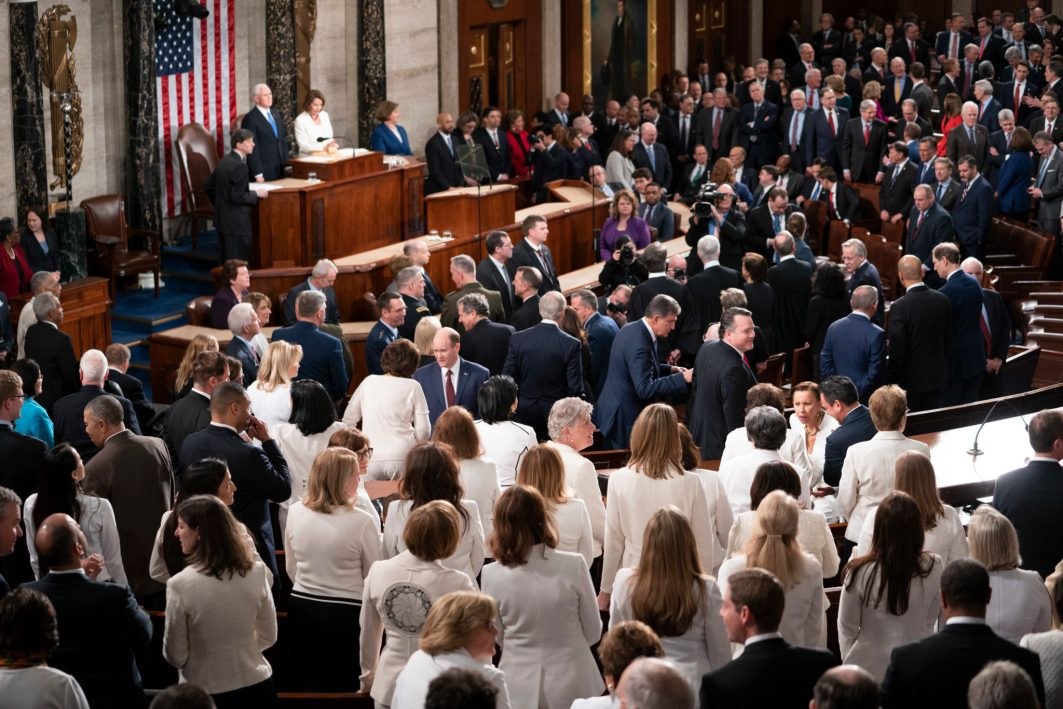 A sea of women Democratic lawmakers dressed in white in the foreground of a view of the House chamber prior to the State of the Union address, February 5, 2019