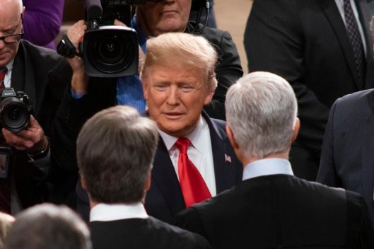 President DONALD TRUMP mingles with House members as he wends his way to the elevated dais to present the State of the Union address, February 5, 2019