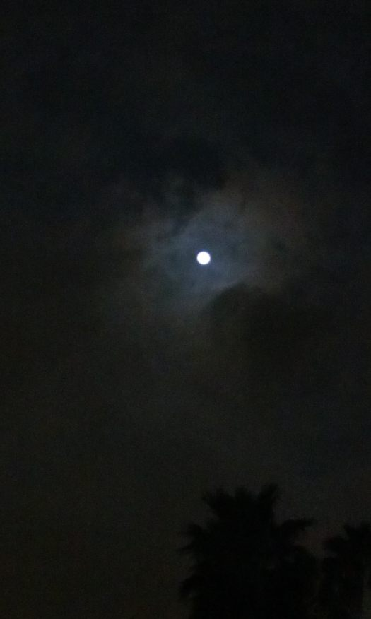 The moon beckons me through the parting in the clouds.