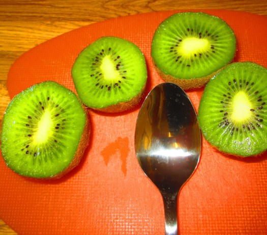 The kiwi fruit is light green with white veins and black seeds.