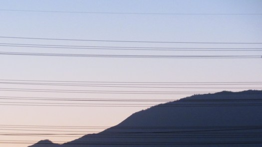 The silhouette of Mount Baldy and power lines in the foreground.