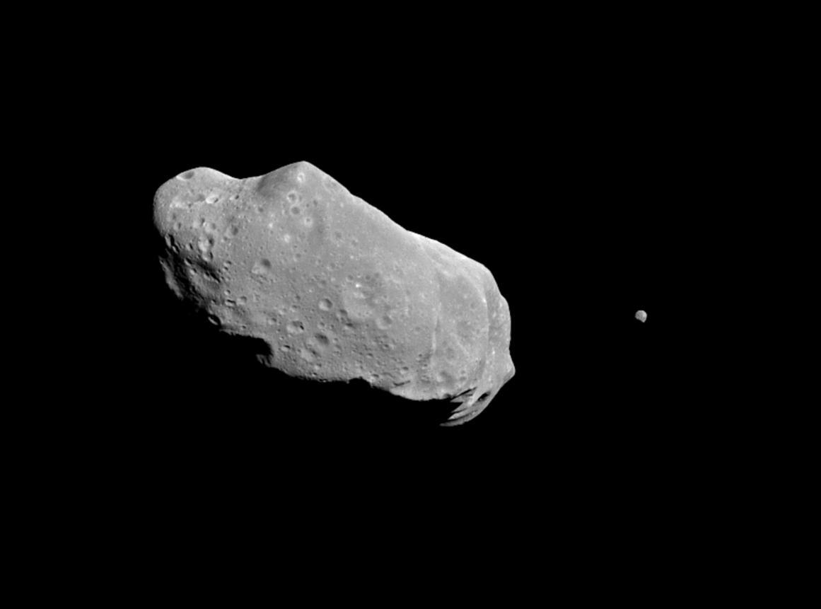 243 Ida (image : via NASA/JPL) fait partie des premiers astéroïdes à avoir été évidé et mis en rotation autour de son axe pour créer une gravité artificielle sur ses parois intérieures. La force centrifuge vous maintient au sol.