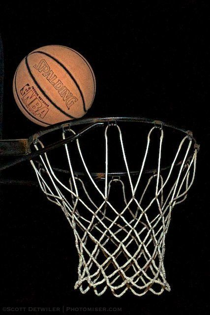 Basketball over the basket in the dark