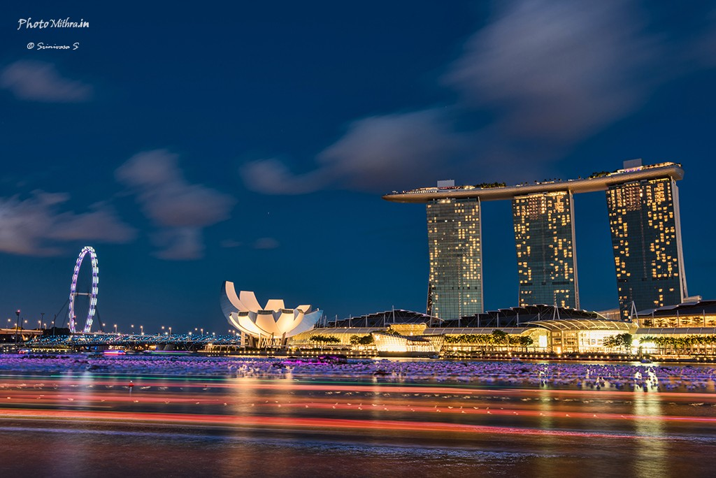 Portrait of Singapore skyline with boats whizzing around in the river