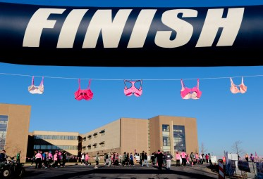 While participants head towards the starting line, a line of bras decorate the finish line for the Care4 Breast Cancer 5K Run/Walk.