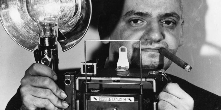 circa 1944: Polish-born American photographer Arthur Fellig (1899 - 1969) with his Speed Graphic camera. He was known by the police as 'Weegee' for his ouija-like prescience of crime scenes and disasters. In fact he kept a radio in his car tuned to the police frequency, and was often able to reach the scene before the police themselves. (Photo by Weegee(Arthur Fellig)/International Center of Photography/Getty Images)