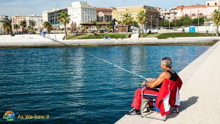 Civitavecchia fisherman sitting on concrete dock