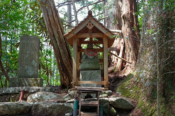 A very cool jizo statue seated within a wooden roof structure.  I wish I were able to read the tablet on the left.