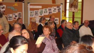 3 dans la salle, 150 personnes regardent un diaporama des 50 ans d'accueil à l'hôtellerie de Lombreuil