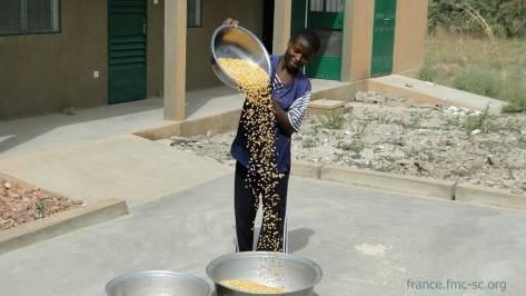 Ange-Prisca entrain de vanner le maïs