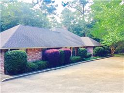 Hidden Beauty on 2 wooded acres!  Close to town, secluded 3/2.5 custom brick home, beautiful landscaping and sprinkler system.  All the extras, plantation shutters throughout the home, Saltillo tile, hardwood floors and new carpet.  There is a large game room, wet bar, great storage, study, gorgeous kitchen w/ commercial gas stove, granite and stainless steel appliances.  Fabulous master suite, large laundry, alarm system, patio, fish pond, circle drive,  2 car garage and separate garage & shop.