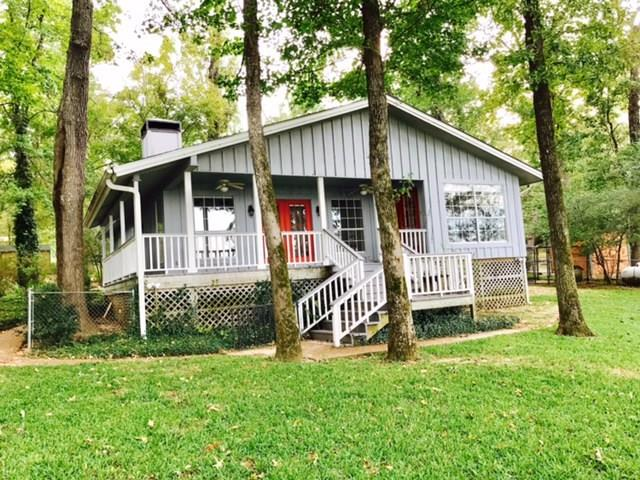 Peaceful Living at Houston County Lake! This property has so much to offer. This pretty waterfront home in desirable Golden Acres Subdivision has a main home and guest house for visitors. The main home has two bedrooms and two baths, nice living room with fireplace and a wall of windows facing the lake. The kitchen has good counter space and is the perfect spot to prepare meals and enjoy your lake view. You will be impressed with the antique stove and stained glass windows throughout the home. Large master suite has good closet space and full bath. The hall bath has a claw foot tub and pedestal sink. The awesome back porch is perfect for relaxation. The lot is fenced, bulk-headed and has a nice pier with covered boat house with two stalls and lifts. The guest house is just off the 3-car garage and has one bedroom and a full bath. There is plenty of parking, a paved driveway, nice landscaping, and a sprinkler system that pumps out of the lake. Come see today!