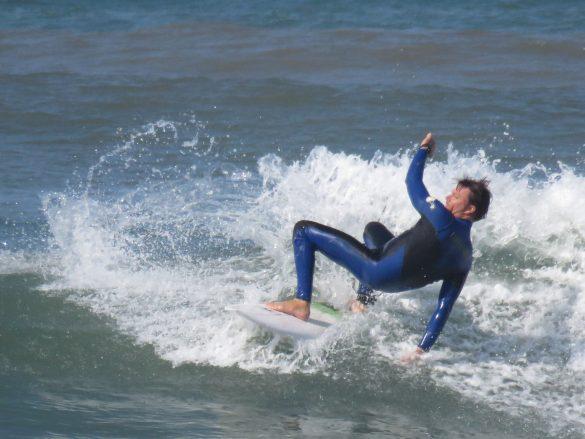Surfer bent over backwards on board