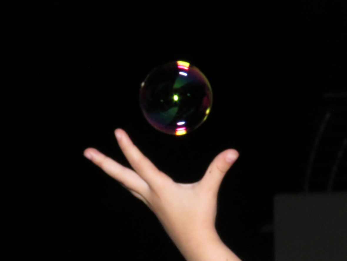 Hand reaching for a soap bubble
