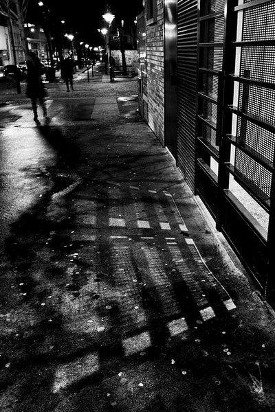 Paris street photography: shadow patterns on wet pavement