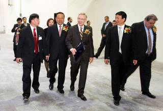 Senate Majority leader Harry Reid, center, arrives with Kai Huang, 2nd left, deputy mayor of Shenyang, China, Jinxiang Lu, 2nd right, chairman/CEO of A-Power, and Tom Conway, right, international vice president of the United Steelworkers union, for the dedication of a new A-Power Energy Generation Systems manufacturing facility in Henderson Tuesday, October 12, 2010. A translator is at far left. The company, based in China, will produce wind turbines and LED lighting.