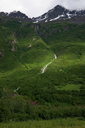 Entering the Chugach Mountains, cascades through green hillsides fed by snowpack high up on the rocky mountains.