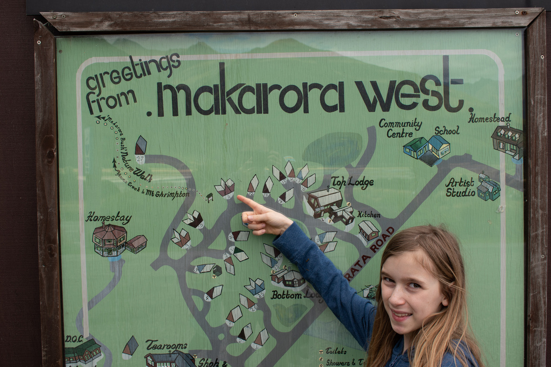 New Zealand South Island Tour - Makarora West. A young girl points to a hand-drawn map of Makorora West, New Zealand, and the tourist centre near Highway 6.
