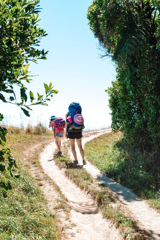 Abel Tasman Coast Track - Great Walks NZ. A mother and daughter hike up a steep, dusty trail along the coastal hiking trail in the Abel Tasman National Park. The pair carry full backpacks as they set out on a 15-mile round trip hike to Mutton Cove.