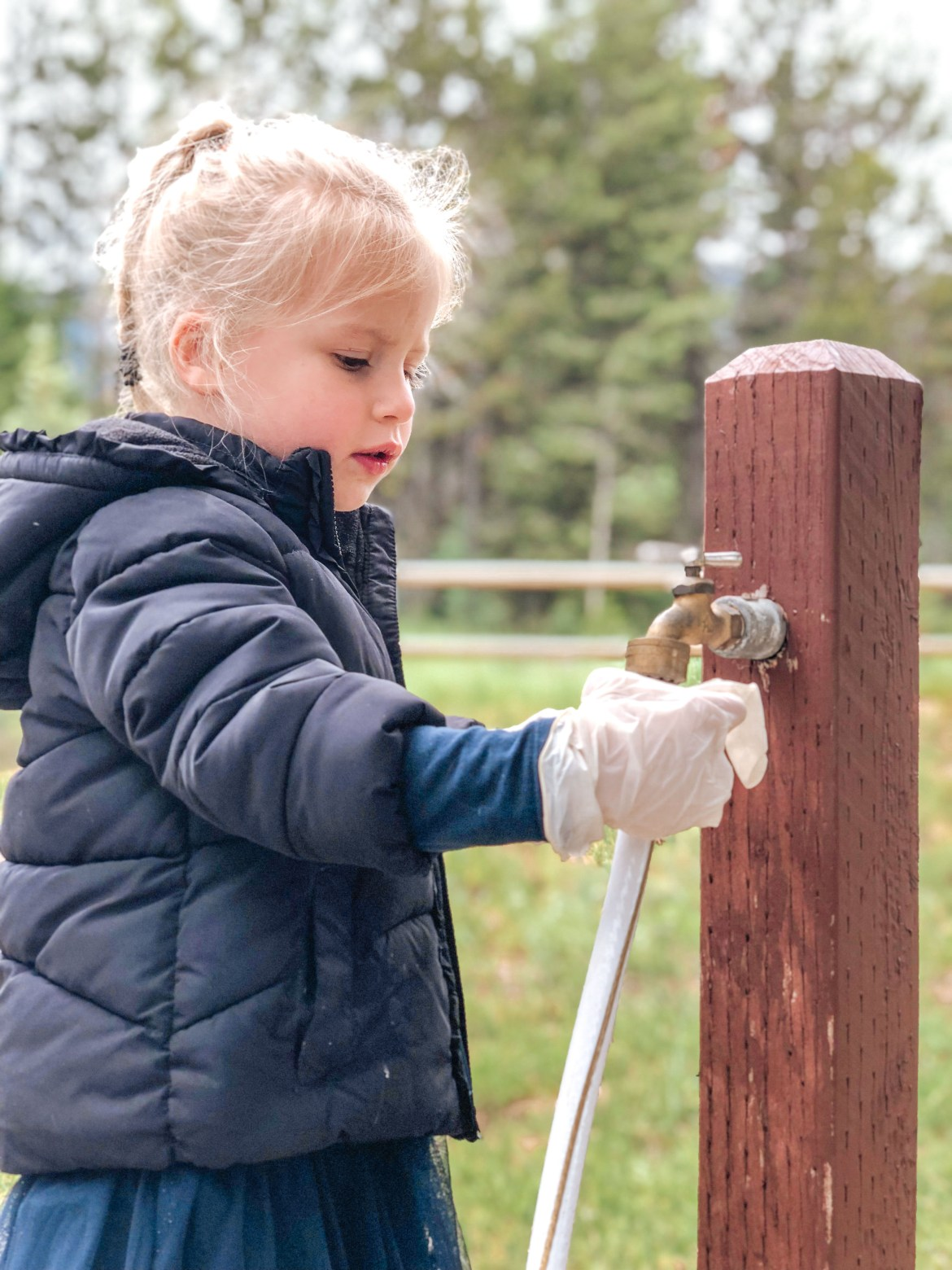 Best Camping in Idaho - Lake Cascade State Park.  A young girl tightens a white water hose to a spigot connected to a wooden post while wearing white latex gloves that are too large for her hands.  She stands at a campsite at Idaho's Cascade Lake State Park near Tamarack Resort and Donnelly, Idaho.